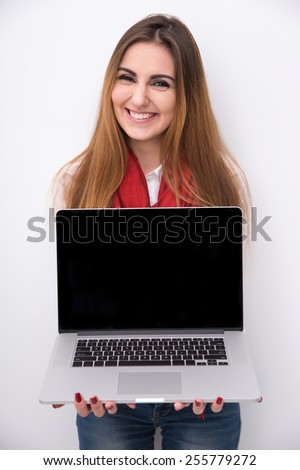 Cheerful beautiful woman showing blank laptop screen - stock photo