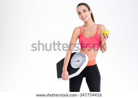Cheerful beautiful young fitness woman in tracksuit holding weighing scale and yellow apple over white background - stock photo