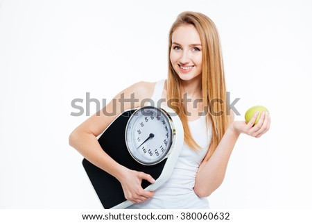 Cheerful beautiful young woman holding scales and green apple over white background - stock photo