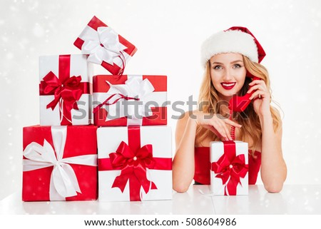 Cheerful beautiful young woman in santa claus costume holding present boxes and talking on telephone over white background
