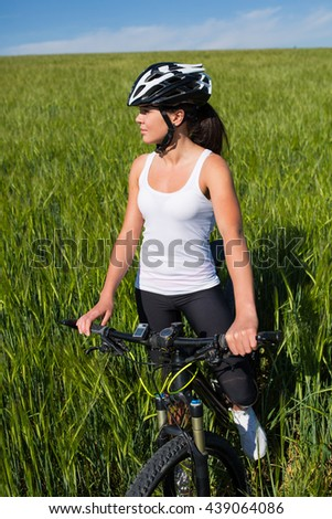 Cheerful beautiful young woman in white shirt with a bike and helmet on a field smiling against blue sky - stock photo