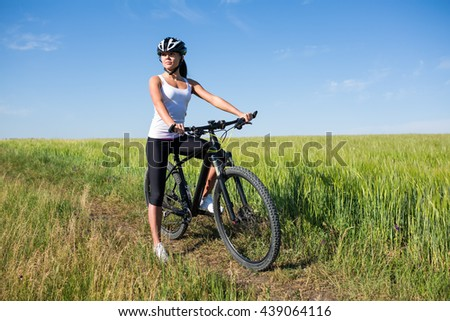 Cheerful beautiful young woman in white shirt with a bike and helmet on a field smiling against blue sky