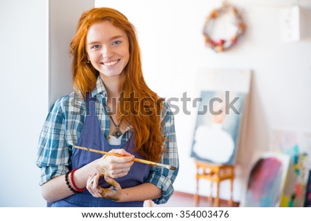 Cheerful beautiful young woman painter with long red hair holding brush and standing in art studio - stock photo