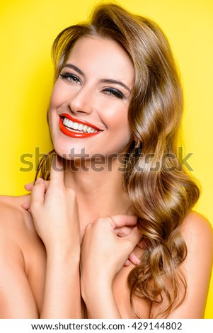 Cheerful beautiful young woman with charming smile over yellow background. Beauty, fashion. Cosmetics, make-up. - stock photo