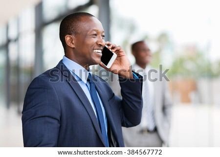cheerful black businessman talking on cell phone - stock photo