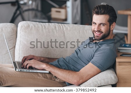 Cheerful blogger. Side view of handsome young man using his laptop and looking at camera with smile while sitting on the couch at home - stock photo
