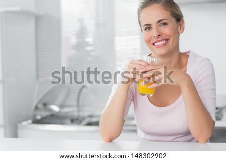 Cheerful blonde having orange juice in her kitchen - stock photo