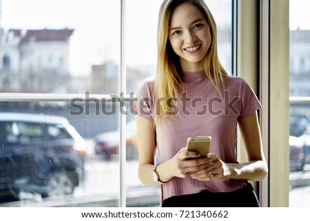 Cheerful blonde hipster girl using phone application for chatting in social networks standing near copy space for advertising, portrait of attractive young student standing on promotional background