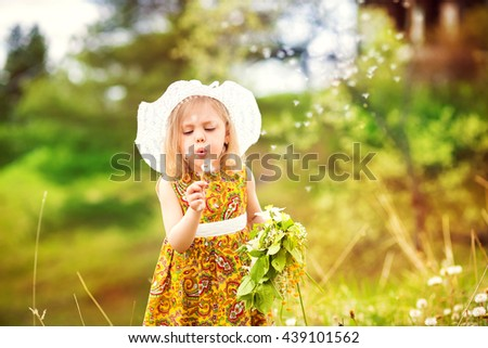 cheerful blonde little girl in a hat with a brim and yellow dress in a flowery garden stands and smiles - stock photo