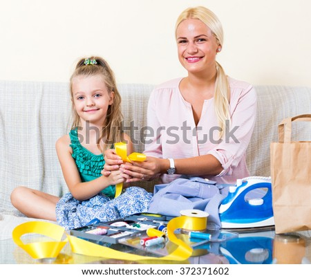 Cheerful blonde mother and little girl working with textile indoors