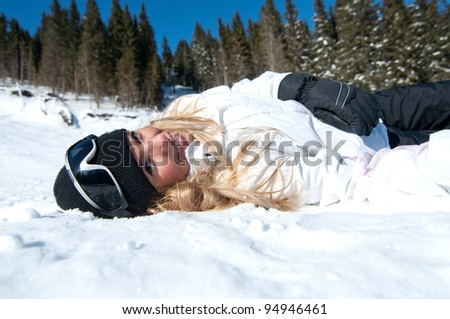 Cheerful blonde skier resting  on snowy slope - stock photo