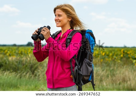Cheerful blonde woman is standing in the nature and holding binoculars.Enjoying nature with binoculars  - stock photo