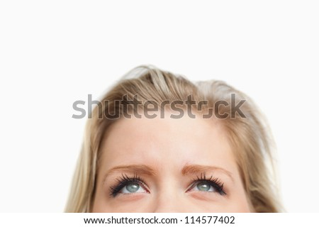 Cheerful blonde woman looking up against a white background
