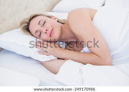 Cheerful blonde woman lying in bed at home in the bedroom - stock photo