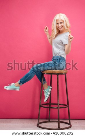 Cheerful blonde woman sitting on the chair over pink background
