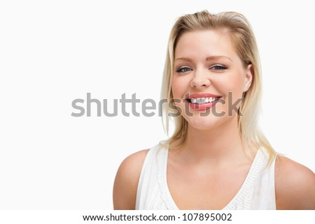 Cheerful blonde woman standing upright against a white background