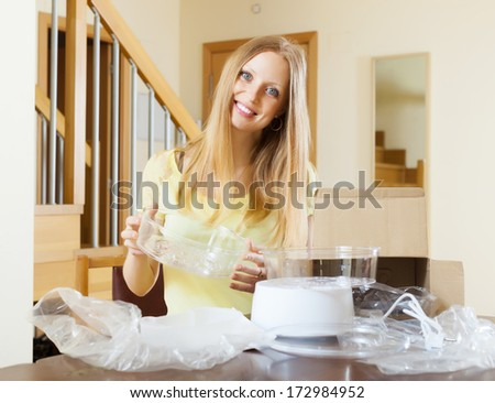 cheerful blonde woman unpacking new electric steamer at home