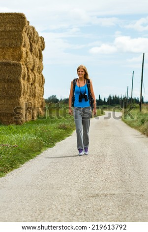 Cheerful blonde woman with backpack and binoculars enjoys walking the country road,Walk the country road - stock photo