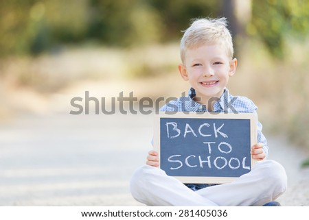 "cheerful boy holding blackboard with ""back to school"" sign - stock photo"