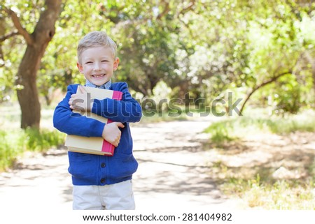 cheerful boy holding book ready for school - stock photo
