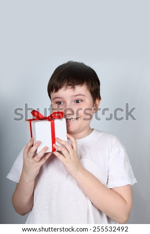 Cheerful boy in a white shirt holding a gift - stock photo