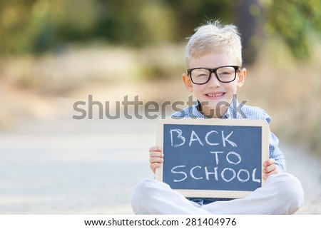 "cheerful boy in glasses holding blackboard with ""back to school"" sign - stock photo"