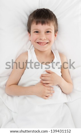 cheerful boy in white bed - stock photo