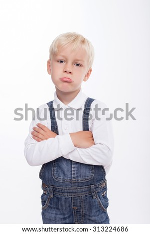 Cheerful boy is resentful. He is looking forward with insult. The boy crossed his hands and pouts. Isolated on background - stock photo