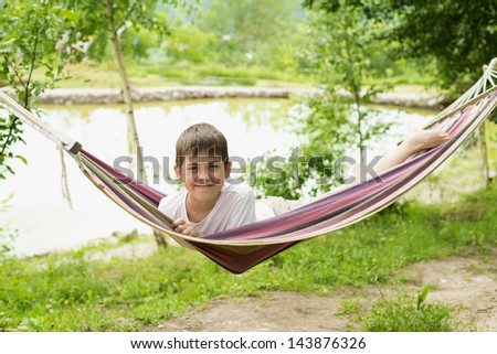 Cheerful boy playing in a hammock on the nature