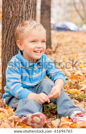 Cheerful boy sitting on yellow foliage in the park. - stock photo