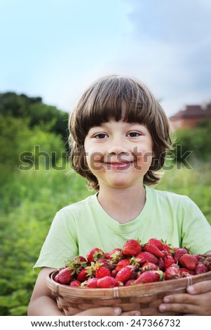 cheerful boy with basket of strawberry - stock photo