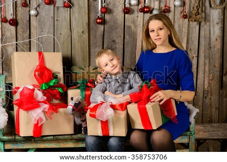 cheerful boy with her mother with Christmas gift in hands - stock photo