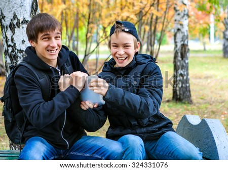 Cheerful Boys Fight for Tablet Computer in the Autumn Park - stock photo