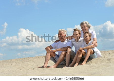 cheerful boys with their grandparents walking on the sand in the summer - stock photo