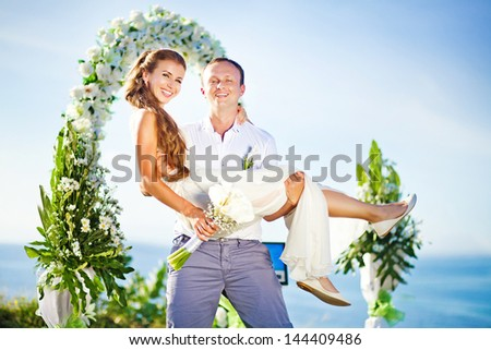cheerful bride and groom on the wedding venue outdoors - stock photo