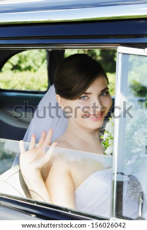 Cheerful bride sitting in the old car - stock photo