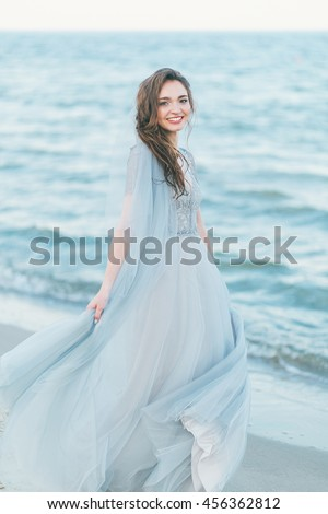 Cheerful bride spinning around at the seashore.