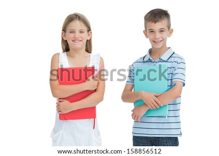 Cheerful brother and sister holding their exercise books while posing on white background - stock photo