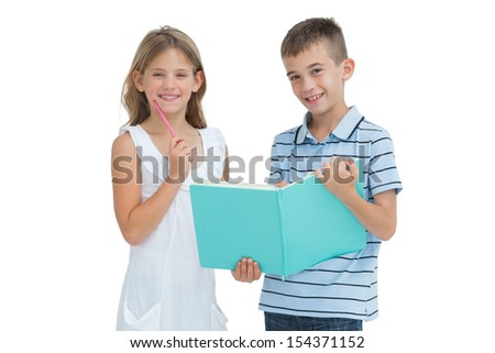 Cheerful brother and sister learning their lesson together while posing on white background - stock photo