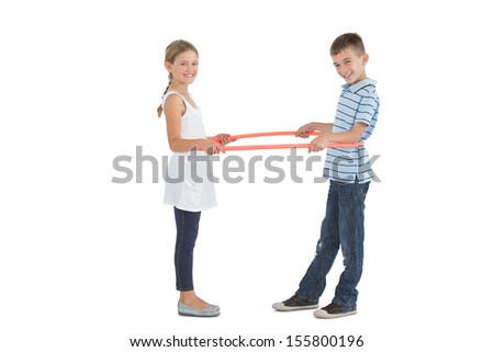 Cheerful brother and sister playing with hula hoop together on white background