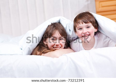 Cheerful brother and  sister under blanket in bedroom - stock photo