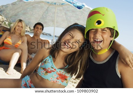 Cheerful brother and sister with parents in background on beach