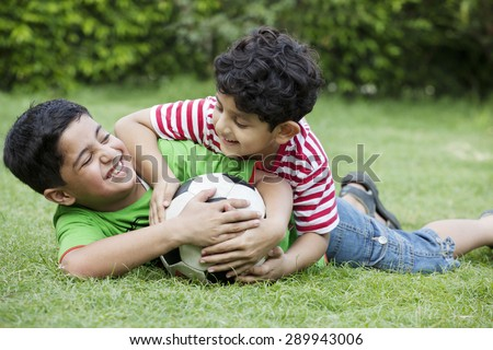 Cheerful brothers playing with soccer ball in park - stock photo