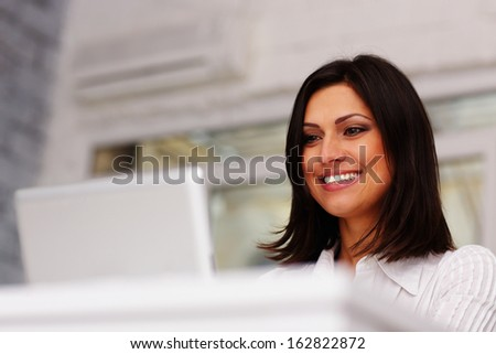 Cheerful brunette businesswoman working on laptop computer in office - stock photo