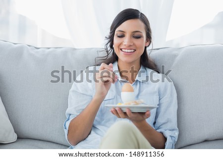 Cheerful brunette eating egg in her living room - stock photo