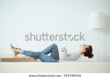 Cheerful brunette girl is resting at home - stock photo
