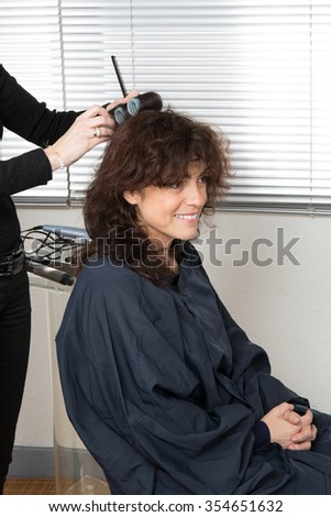 Cheerful brunette girl with hair curlers rollers by hairdresser. Hairstyle. - stock photo