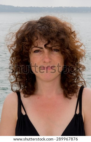 Cheerful brunette looking at the camera on summer - stock photo