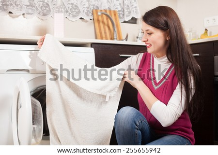 Cheerful  brunette woman doing laundry with washing machine at home - stock photo
