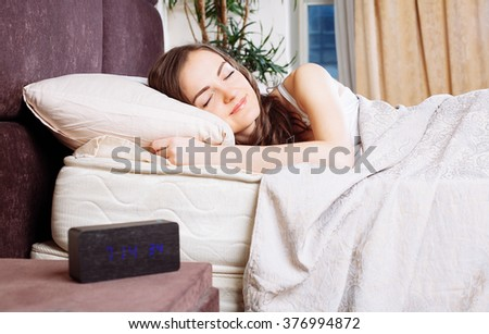 Cheerful brunette woman waking up in the morning with alarm clock  in bed  at home